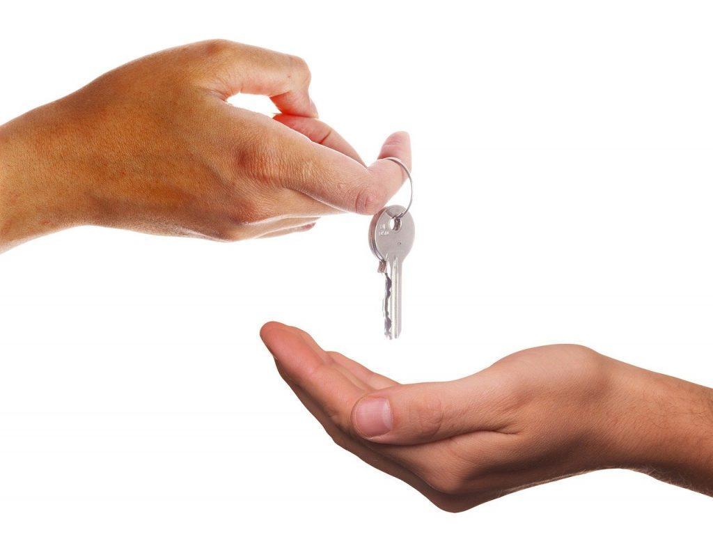 personne qui dépose des clés dans la main d'une autre personne